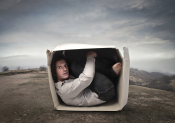 bigstock-Man-crouched-into-a-box-in-a-w-38591734